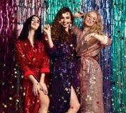 Partei- und Feiertagskonzept Drei Zauberfrauen in den Luxusfunkelnpailletten kleiden Haben des Spa?es lizenzfreie stockfotografie
