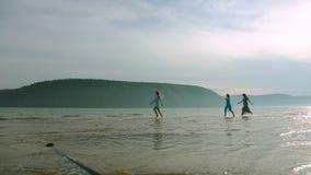 Partei- und Leutekonzept - Gruppe lächelnde jugendlich Mädchen, die auf Strand springen Schattenbild von drei jungen Frauen, die  stock footage