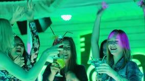 Partei von Freundmädchen hält Gläser mit Alkoholcocktails und -tanzen auf Tanzboden stock footage