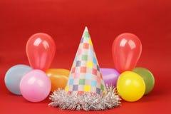 Parteihut und Parteiballone auf rotem Hintergrund Lizenzfreie Stockbilder
