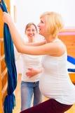 Partera que hace la gimnasia del embarazo para la madre Imagen de archivo