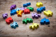 Partes coloridas do enigma no fundo de madeira Enigma de madeira Imagens de Stock Royalty Free
