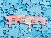 Partes conectadas na pilha de enigmas de serra de vaivém azuis Foto de Stock Royalty Free