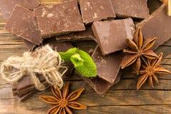 Partes de anis do chocolate, da canela e de estrela em uma tabela de madeira Fotos de Stock