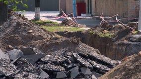 Partes de asfalto quebrado e de um poço escavado com uma fita vermelho-branca protetora vídeos de arquivo