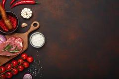 Partes de bife cru da carne de porco na placa de corte com tomates de cereja, alecrins, alho, pimenta vermelha, cebola, sal e esp imagem de stock royalty free