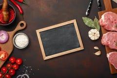 Partes de bife cru da carne de porco na placa de corte com tomates de cereja, alecrins, alho, pimenta vermelha, folha de louro, c fotos de stock royalty free