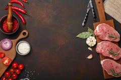 Partes de bife cru da carne de porco na placa de corte com tomates de cereja, alecrins, alho, pimenta vermelha, folha de louro, c fotos de stock
