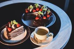 Partes de bolo Café do cacau do chocolate quente da bebida em uns copos Fundo preto Imagens de Stock Royalty Free