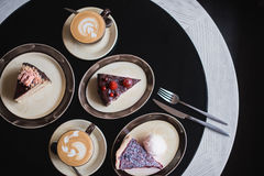 Partes de bolo Café do cacau do chocolate quente da bebida em uns copos Fundo preto Fotografia de Stock Royalty Free