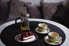 Partes de bolo Café do cacau do chocolate quente da bebida em uns copos Fundo preto Fotos de Stock Royalty Free