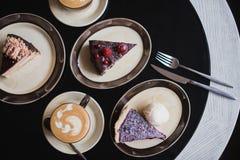Partes de bolo Café do cacau do chocolate quente da bebida em uns copos Fundo preto Fotografia de Stock