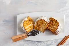 Partes de bolo de cenoura caseiro do vegetariano com creme branco em um branco Fotografia de Stock Royalty Free