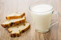 Partes de bolo com passa e o copo transparente com leite Imagens de Stock Royalty Free