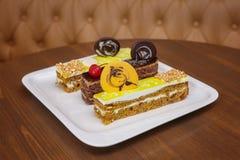 Partes de bolo marrom com doce no prato branco Imagem de Stock