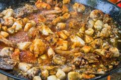 Partes de carne do coelho e da galinha que frita com molho de tomate no azeite na grande bandeja lisa Cozinhando o paella ou o ja Fotografia de Stock Royalty Free