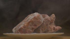 Partes de carne de gerencio congelada em um fundo preto, de que frescor gelado dos sopros e frio, fumo, close-up, lento video estoque