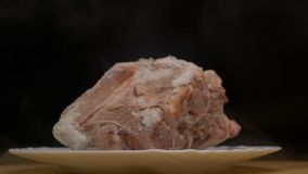 Partes de carne de gerencio congelada em um fundo preto, de que frescor gelado dos sopros e frio, fumo, close-up, lento vídeos de arquivo