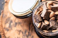 Partes de chocolate amargo escuro com as amêndoas do cacau e das porcas no fundo de madeira Conceito de ingredientes dos confeito imagens de stock royalty free
