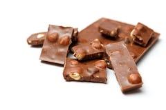 Partes de chocolate com as avelã no fundo branco fotografia de stock