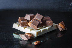 Partes de chocolate de leite com amêndoas e telhas do chocolate branco com avelã em um fundo lustroso velho escuro foto de stock