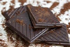 Partes de chocolate escuro com pó do chocolate Imagem de Stock