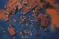 Partes de chocolate, de feijões de café roasted e de pó de cacau em um fundo azul Vista superior, configuração lisa imagens de stock