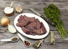 Partes de fígado cru fresco da carne, cebola, alho, especiarias, aneto, salsa, sal, faca, azeite na placa da porcelana em um back imagem de stock