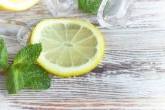 Partes de limão com cubos de gelo em um close-up de madeira velho da tabela Limão cortado com hortelã o conceito dos refrescos fotos de stock royalty free