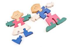 Partes de madeira coloridas do enigma da menina e do menino Fotos de Stock
