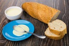 Partes de pão, bacia com leite condensado, colher com leite imagem de stock