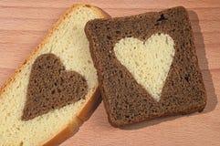 Partes de pão marrom e branco com os corações Imagem de Stock
