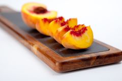 Partes de pêssegos em uma placa de corte Imagem de Stock