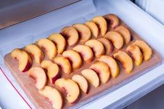Partes de pêssegos em uma placa de corte em um congelador Foto de Stock