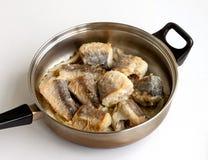 Partes de peixes fritados em uma frigideira Imagem de Stock