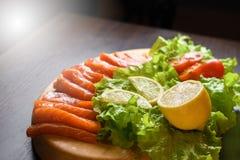 Partes de peixes vermelhos com os tomates do limão e de cereja em uma placa de madeira fotografia de stock royalty free