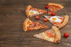 Partes de pizza diferente em uma tabela de madeira Imagem de Stock
