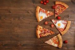 Partes de pizza diferente em uma tabela de madeira Fotos de Stock