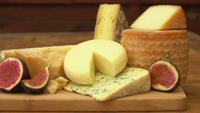 Partes de queijo e de figos em uma tabela de madeira vídeos de arquivo
