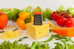 Partes de queijos, de queijo raspado, de grelha do metal, de faca, de tomates, de pimentas e de folhas dos frillis e da rúcula Imagem de Stock