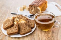 Partes de queque na placa branca, copo do chá Fotografia de Stock Royalty Free