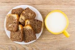 Partes de queque na placa e no copo brancos do leite Foto de Stock