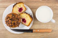 Partes de queques na placa, na faca de cozinha e no leite Foto de Stock