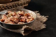 Partes de salsicha fritadas com cebolas Foto de Stock