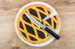 Partes de torta da uva-do-monte na faca do prato e de cozinha Fotografia de Stock