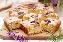 Partes de torta do fruto com partes de ameixas e de pêssego e de um ramalhete das flores em uma tabela de madeira Estilo rústico Fotografia de Stock Royalty Free