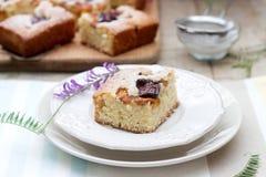 Partes de torta do fruto com partes de ameixas e de pêssego e de um ramalhete das flores em uma tabela de madeira Estilo rústico Imagens de Stock