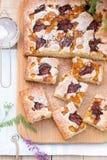 Partes de torta do fruto com partes de ameixas e de pêssego e de um ramalhete das flores em uma tabela de madeira Estilo rústico Imagens de Stock Royalty Free