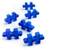 Partes de um enigma de serra de vaivém colorido no fundo branco Barreiras da ruptura junto para o conceito do autismo Fotos de Stock Royalty Free