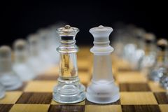 Partes de xadrez da rainha que estão próximos um do outro, partes de xadrez geladas da rainha em um fundo preto fotografia de stock